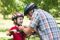 Father attaching his sons cycling helmet on a sunny day